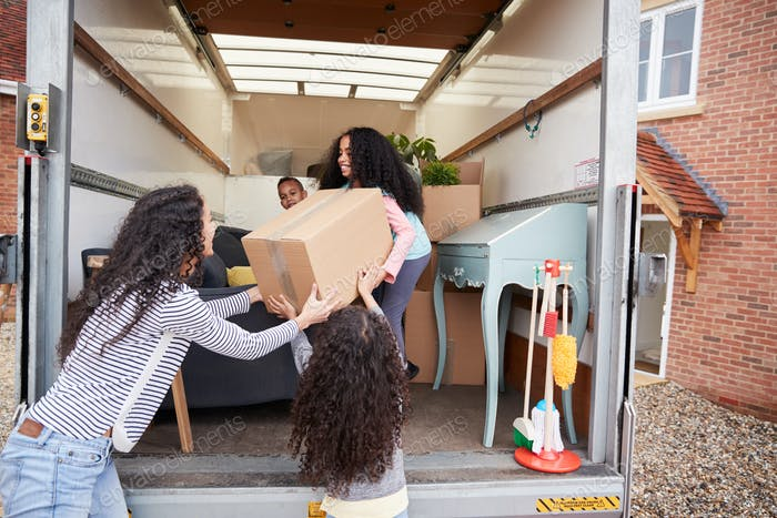 Mother And Children Unloading Furniture From Removal Truck Into New Home