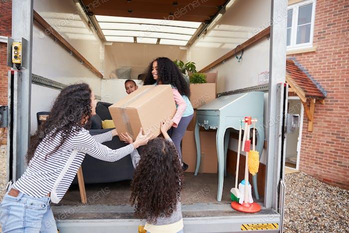 Mutter und Kinder Entladen Möbel aus der Entfernung LKW in neues Zuhause