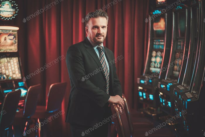 Elegant man near slots machines in a luxury casino interior