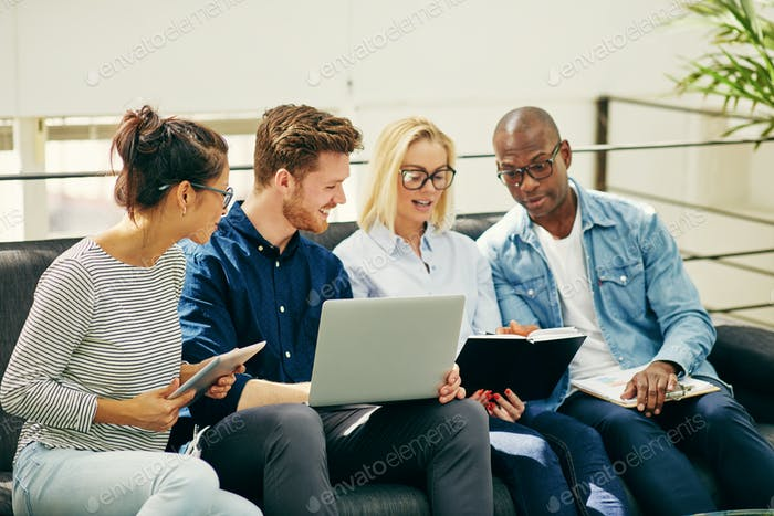 Diverse young businesspeople discussing work together on an office sofa