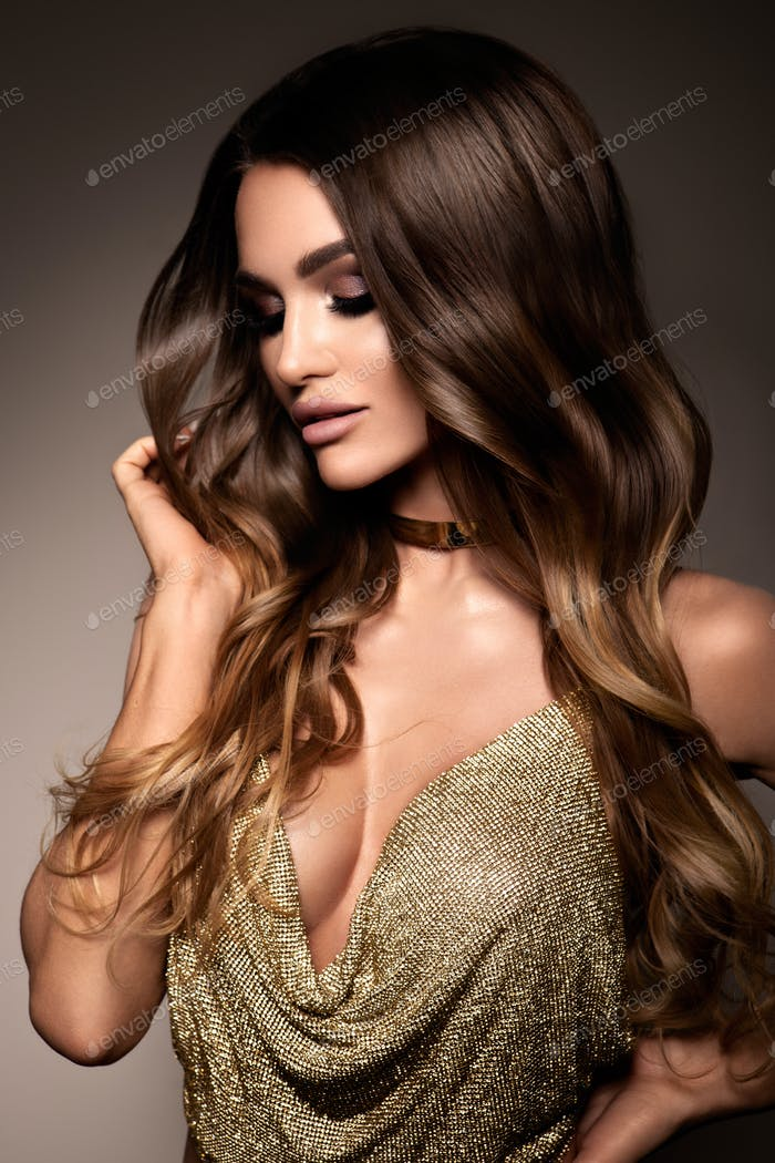 Fashion portrait of young beautiful woman in gold dress.