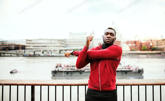 Young sporty black man runner doing stretching on the bridge outside in a city.