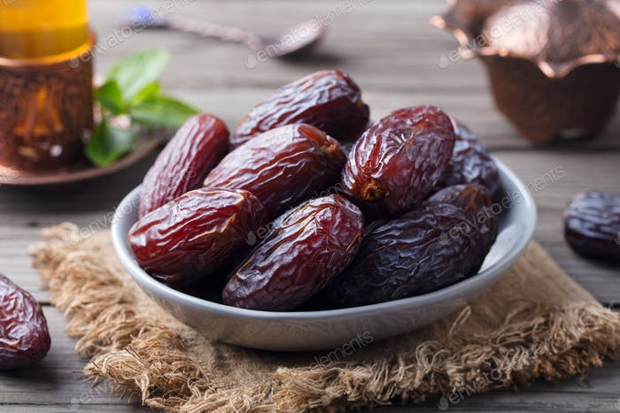 Fresh Medjool Dates in a Bowl with Tea. Ramadan Kareem. Grey Wooden Background.