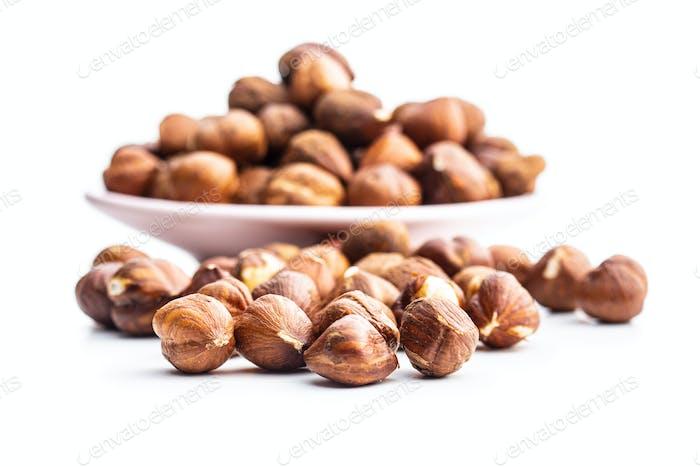 Peeled hazelnuts on white background.