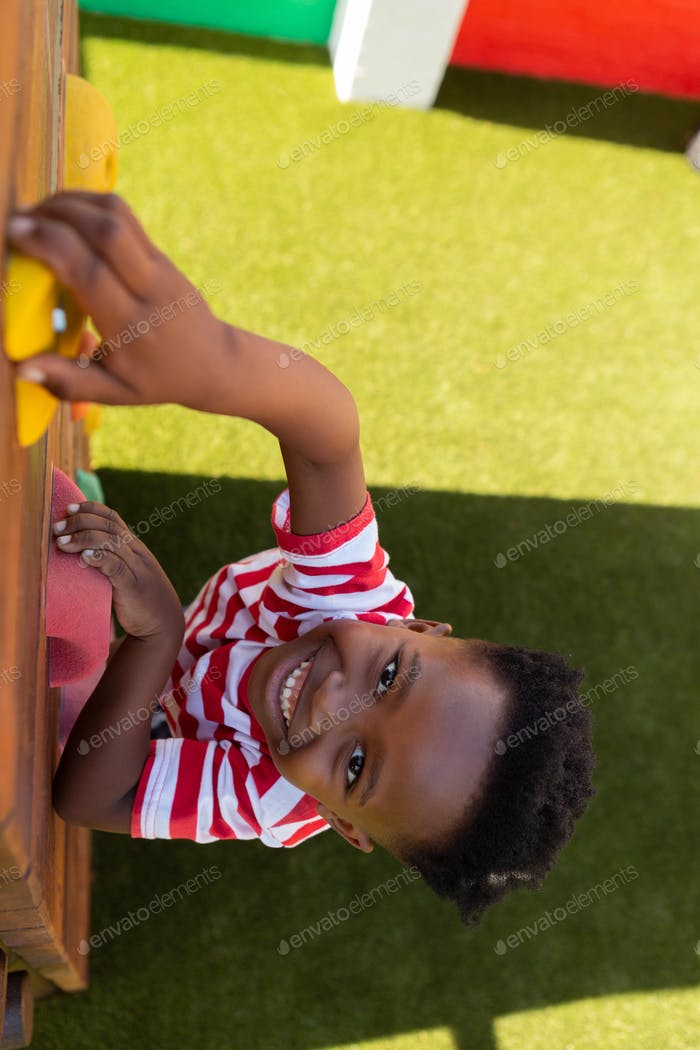 Smiling African American schoolboy climbing a wall in the school playground on a sunny day