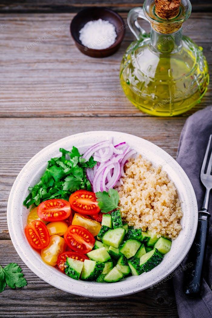 Saludable Quinoa Tabbouleh Ensaladera con pepinos frescos, tomates y cebollas rojas