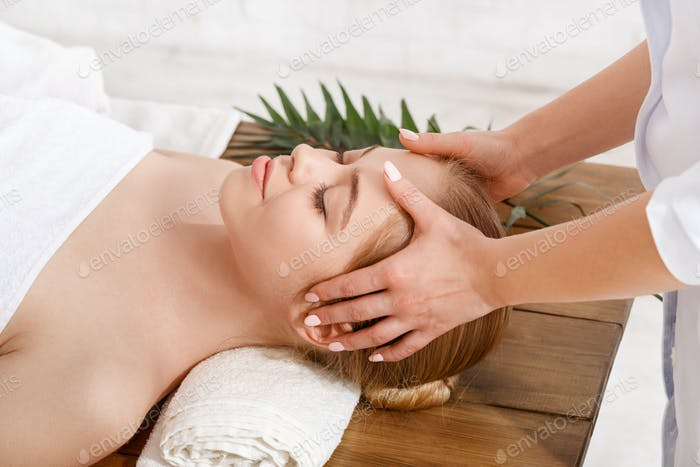 Beauty treatments. Professional doing facial massage for girl on table