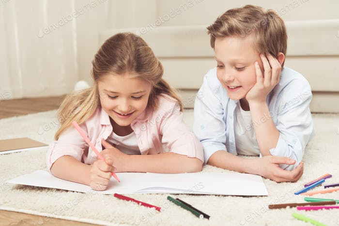 adorable pre-adolescent kids drawing pictures while lying on the floor at home