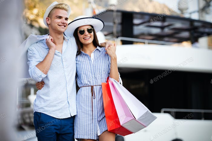 Beautiful loving couple carrying shopping bags and enjoying together