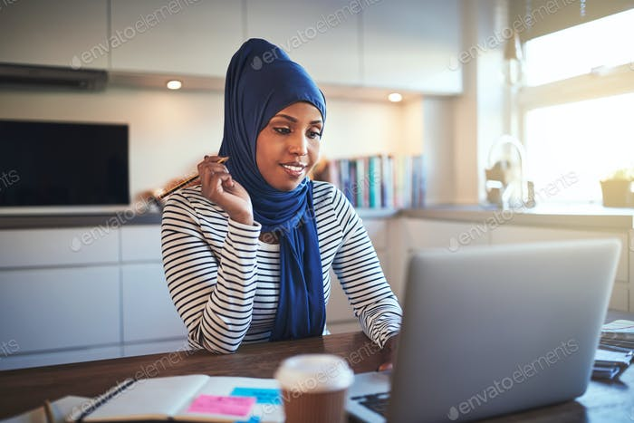 Young Arabic entrepreneur working on a laptop in her kitchen