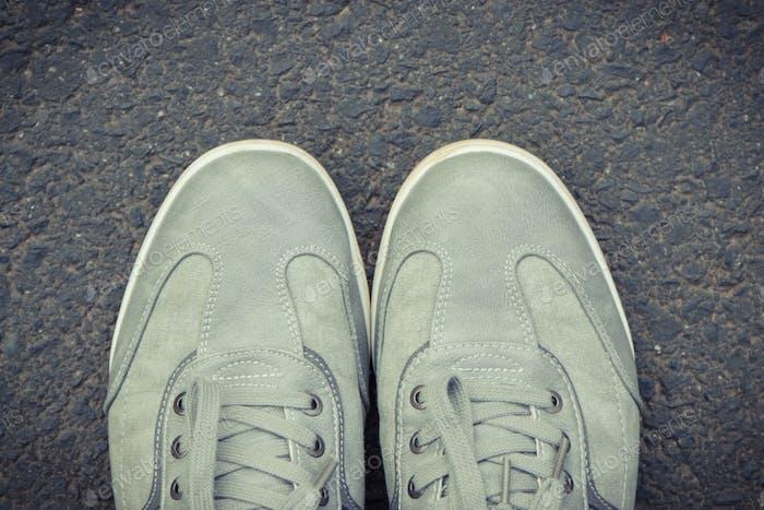 Graue Lederschuhe auf Asphaltstraße oder Fußweg. Männliche Schuhe