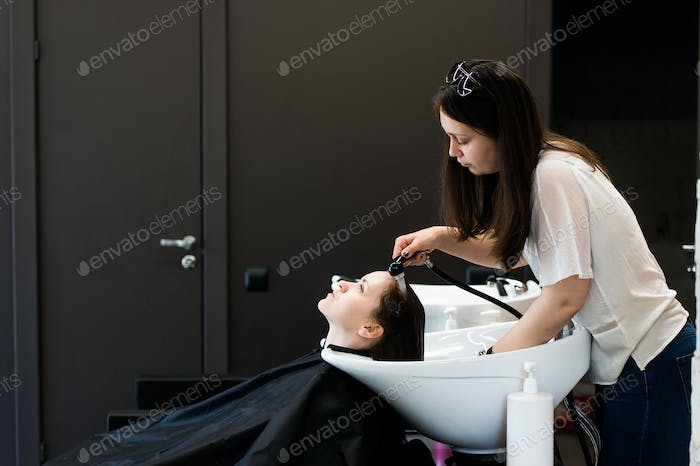 Young female stylist drying woman hair with water in salon barbershop