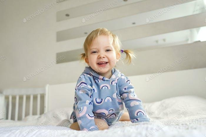 Adorable niña en casa en la cama