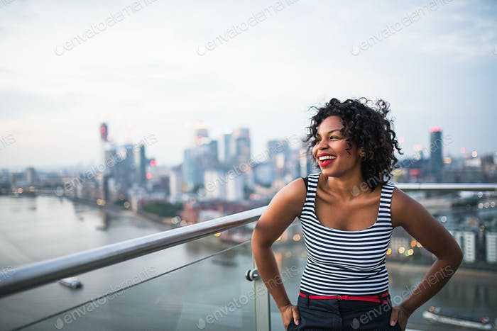 Thumbnail for A portrait of businesswoman standing against London rooftop view panorama.