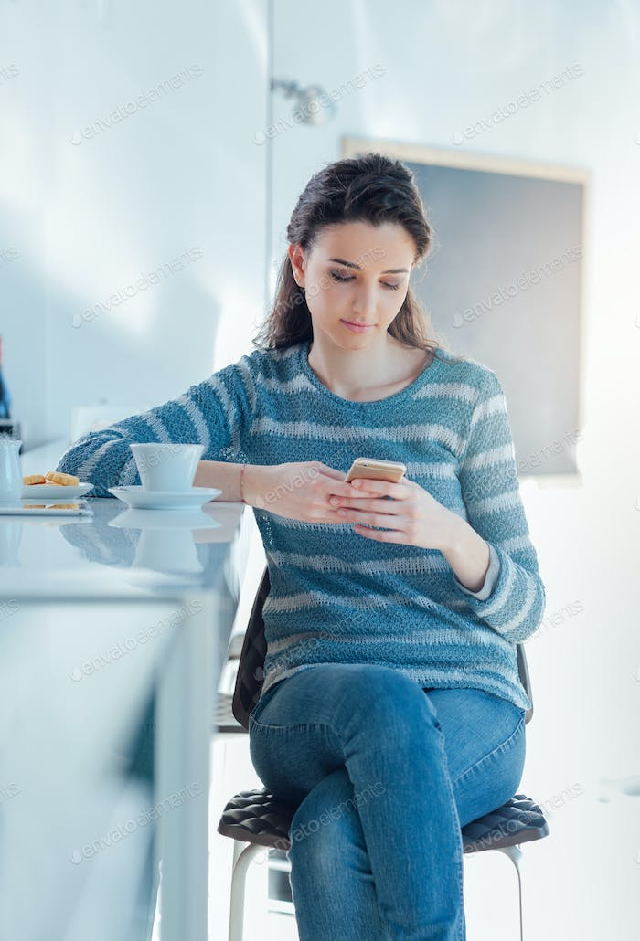 Teenager girl at the bar texting with her mobile