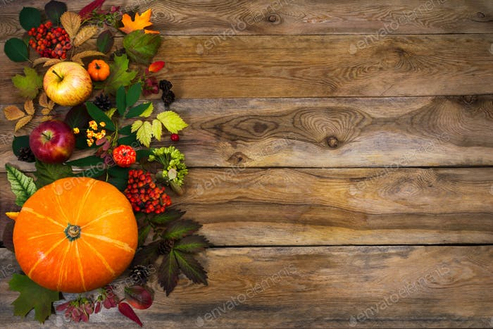 Thanksgiving decor with leaves and squash on wooden table