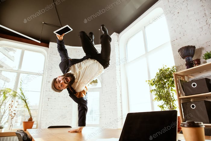 Businessman having fun dancing break dance in the office at work
