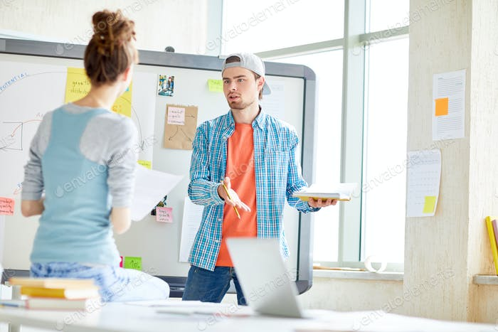 Pensive guy arguing with colleague in office