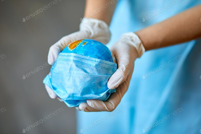 Globe in einer medizinischen Maske in den Händen des Arztes