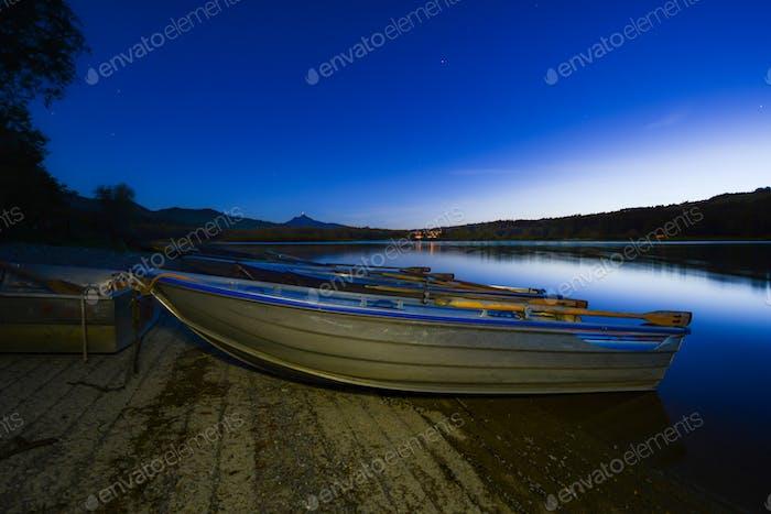 Illuminated rowboats at a lake at night
