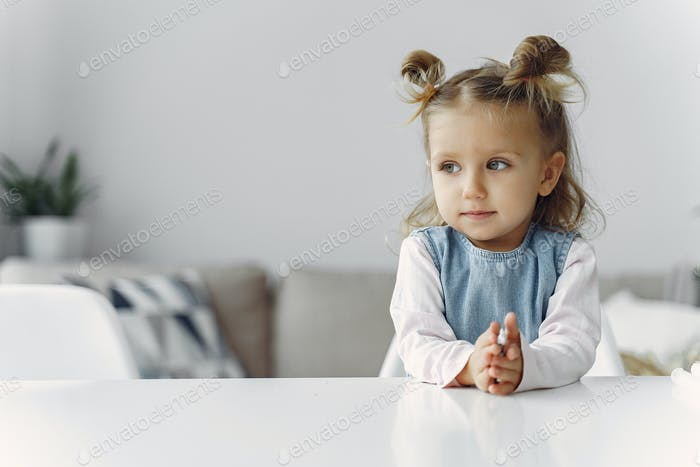 Kleines Mädchen sitzt auf einem Tisch mit Spielzeug