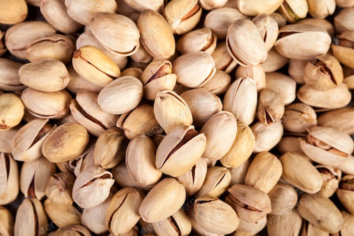 Close up of Pistachios on wooden background in studio photo