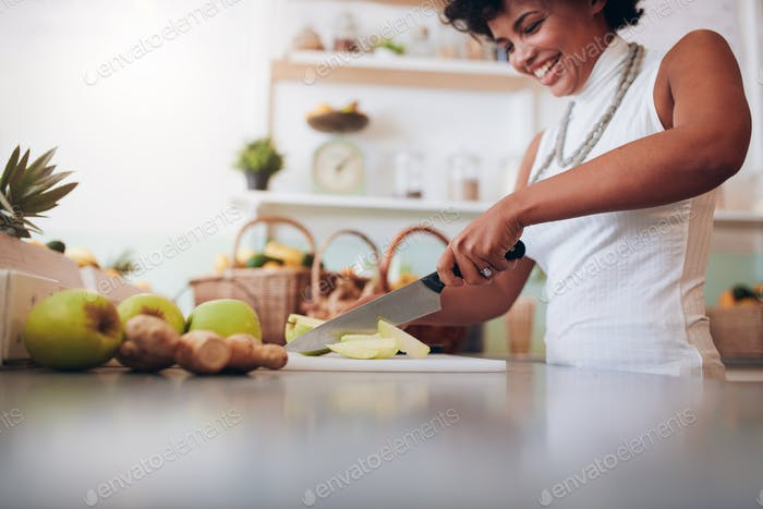 Young african woman making fresh juice