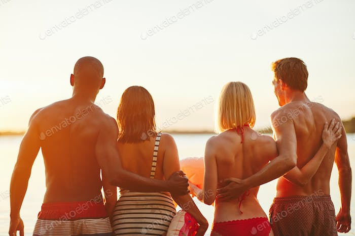Two couples in swimsuits watching the sunset over a lake