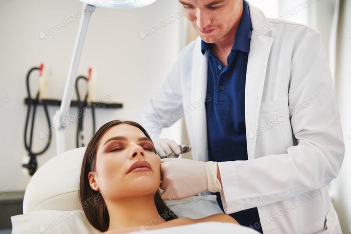 Male doctor doing botox injections on a young female client