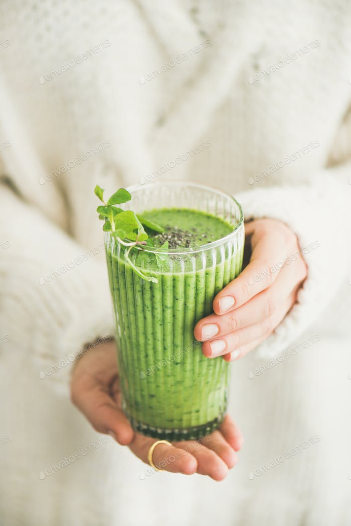 Matcha green smoothie with chia seeds in womans hands