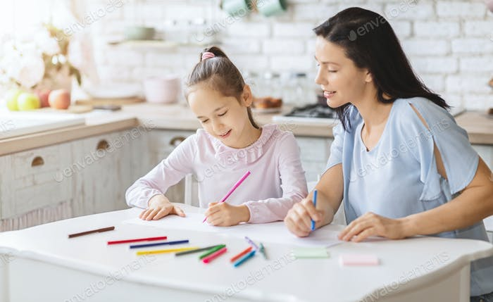 Mother drawing with her daughter on kitchen table