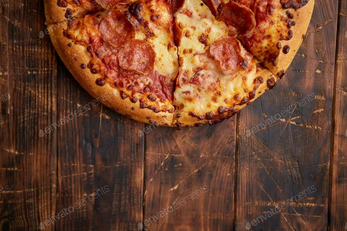 Fluffy pepperoni pizza in american style placed on rusty old wooden table