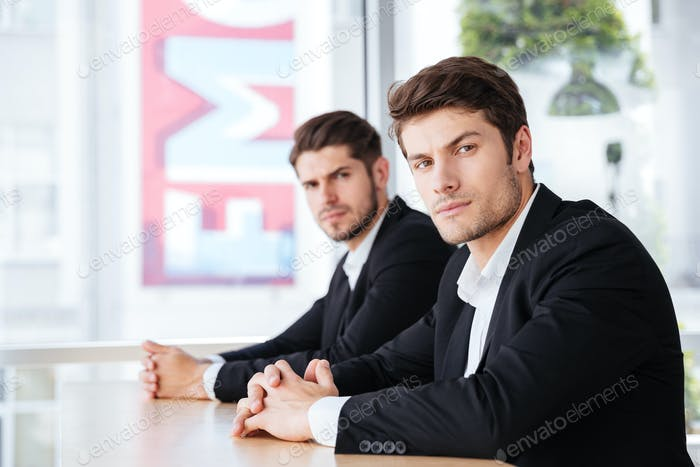 Two confident businessmen in suit sitting in office together
