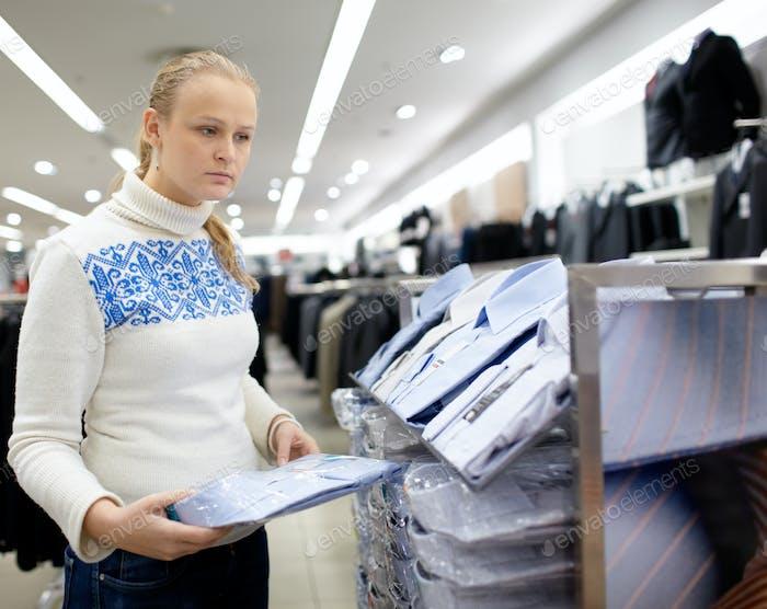 Die Frau wählt Hemd für den Mann