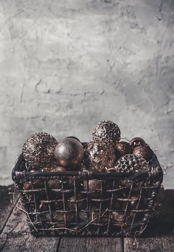vintage christmas, new Year toys and decoration in basket on brown wooden table with garlands