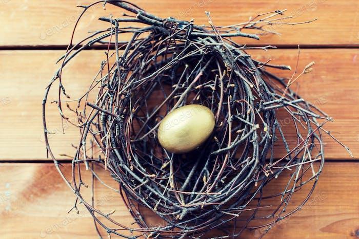 close up of golden easter egg in nest on wood