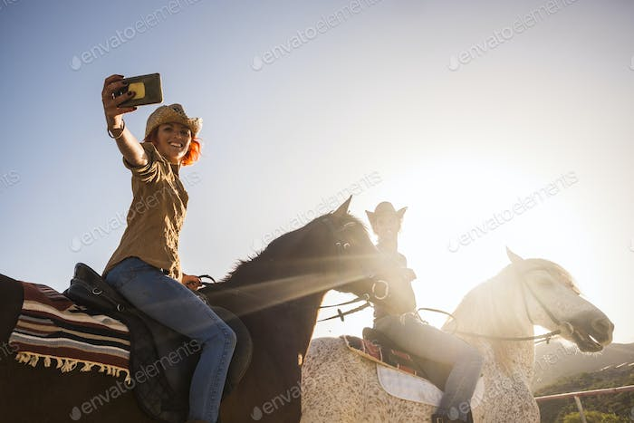 couple on horses riding outdoor under the sunlight in backlight