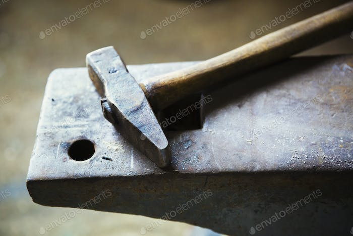 A hammer on top of an anvil.