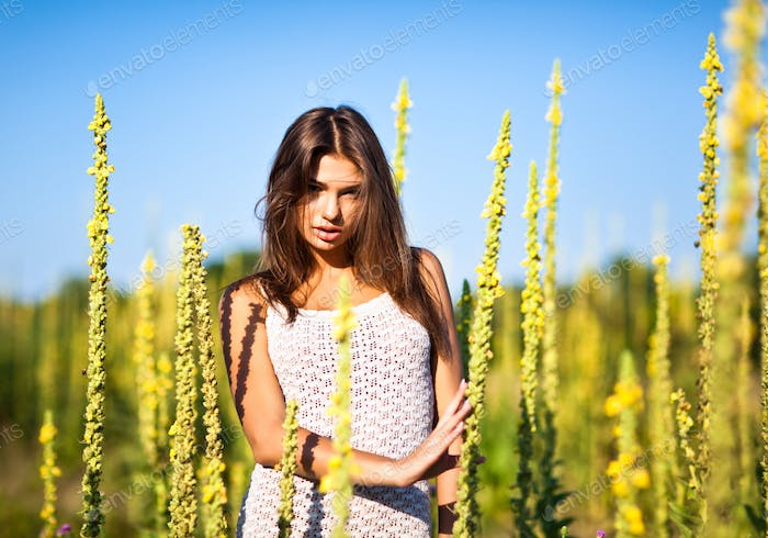Young sexy woman in white mini dress standing with eyes closed and enjoying sunshine in high grass