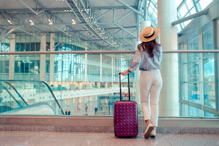 Young woman in hat with baggage in international airport