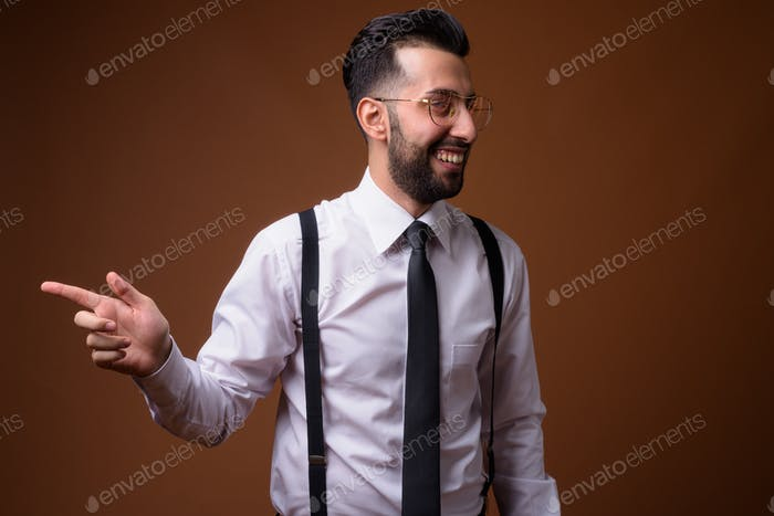 Young handsome bearded Iranian businessman against brown backgro