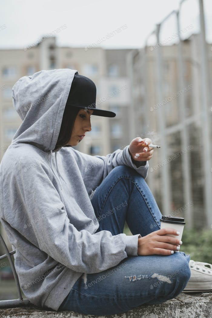Woman smoking cigarette and drinking coffee