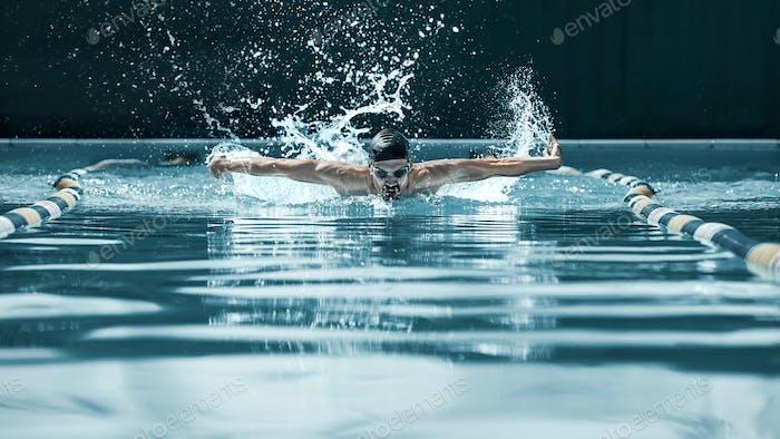 dynamische und fit Schwimmer in Kappe Atmung Durchführung der Schmetterling Schlaganfall