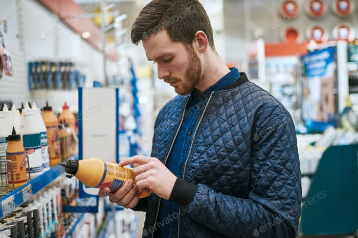 Man selecting a product in a hardware store