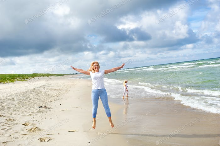 Young woman jumping on the beach of the Baltic Sea in Lithuania. Little girl stroll along the beach