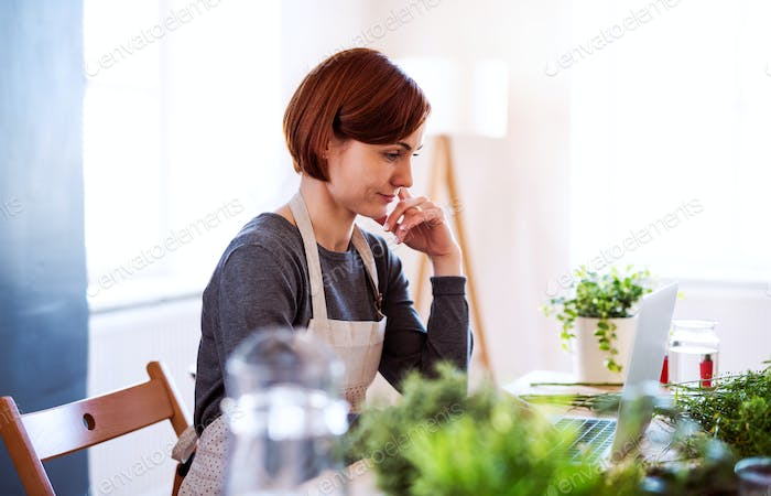 Young creative woman in a flower shop, using laptop. A startup of florist business.