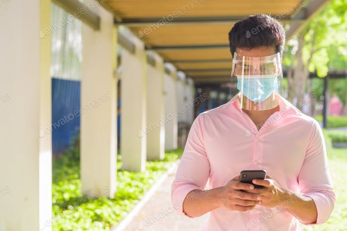 Young Indian businessman with mask and face shield using phone at the park outdoors