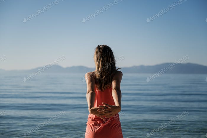 Young woman stretching arms by the morning sea