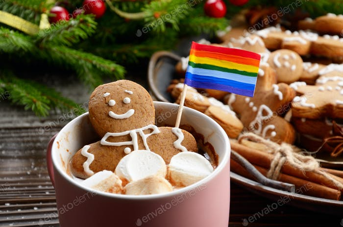 Pink mug with hot chocolate marshmallows and gingerbread man with rainbow flag