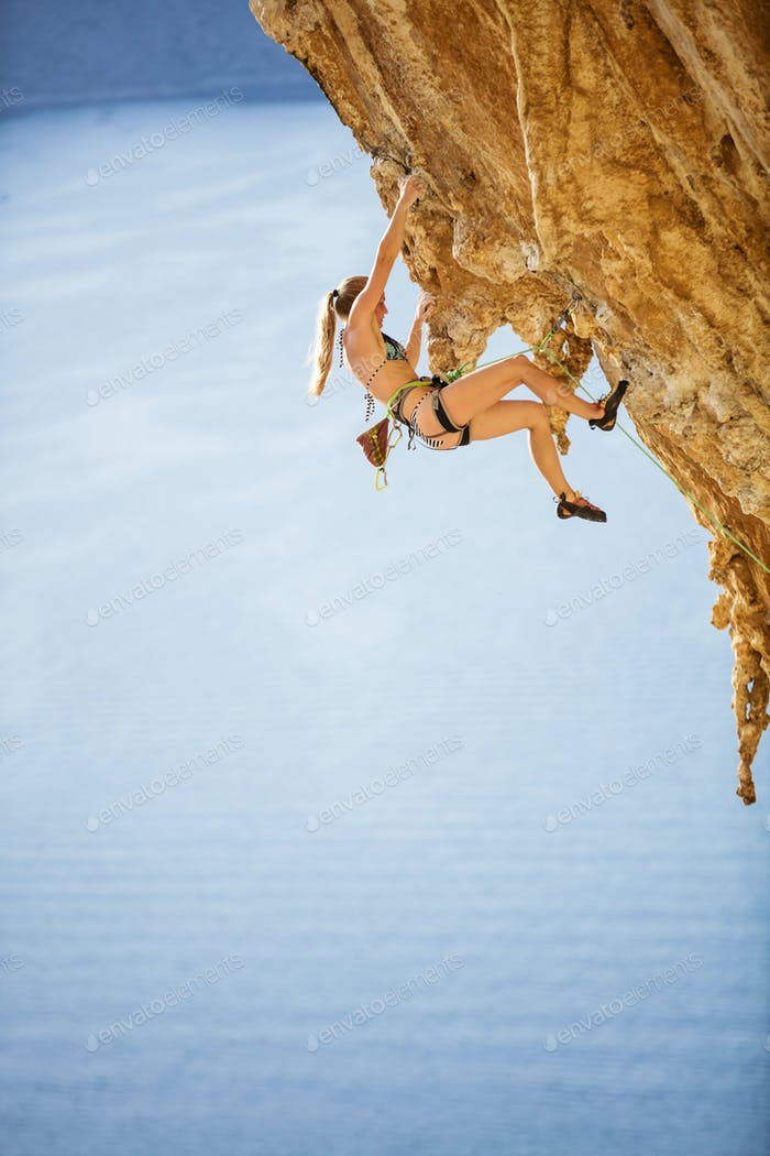 Young woman in bikini climbing challenging route